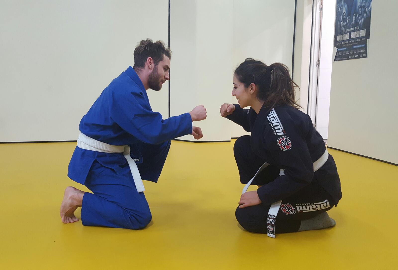 chica y chico practicando jiu jitsu brasileño